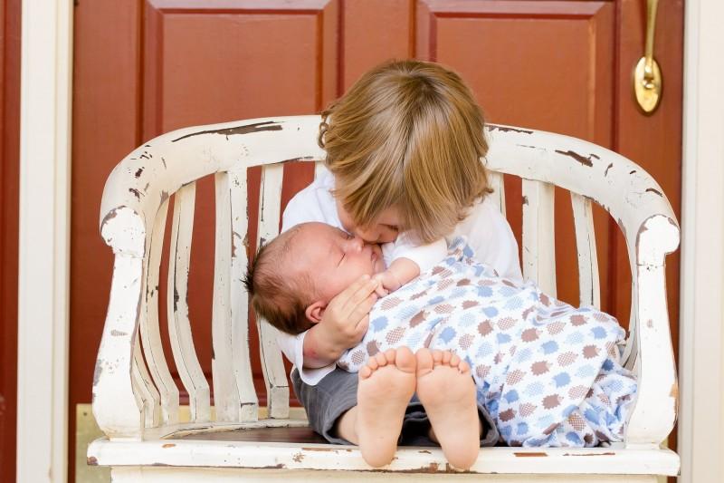 toddler boy holding baby