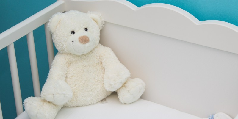 teddy bear in baby crib